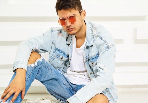 Retrato de hombre joven y guapo modelo vestido con ropa de jeans sentado cerca de la pared blanca con textura