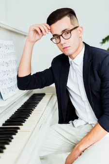 Retrato de hombre joven guapo sentado cerca del piano con hoja musical
