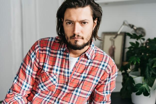 Retrato de un hombre joven hermoso en la camisa de tela escocesa que mira la cámara