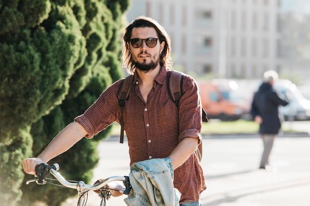 Retrato de un hombre joven hermoso que camina con la bicicleta en el camino