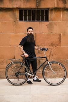 Retrato de un hombre joven hermoso que se coloca con su bicicleta delante de la pared