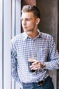 Retrato de un hombre joven hermoso que se inclina en la ventana que sostiene el vidrio de cerveza