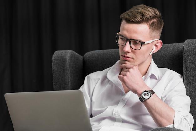 Retrato de un hombre joven hermoso que se sienta en la butaca que mira la computadora portátil