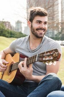 Retrato del hombre joven hermoso que toca la guitarra en el parque
