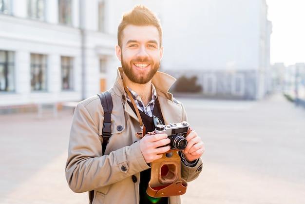 Retrato de un hombre joven hermoso sonriente que se coloca en la ciudad que sostiene la cámara disponible