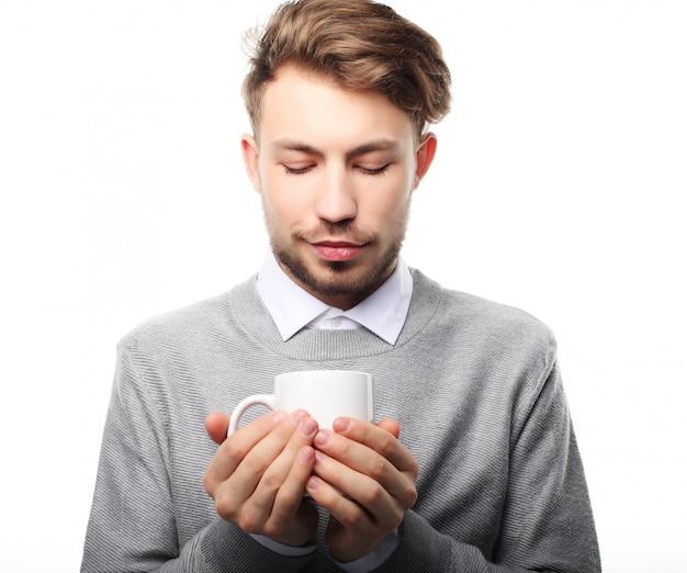 Retrato del hombre joven hermoso con la taza, aislado en blanco.