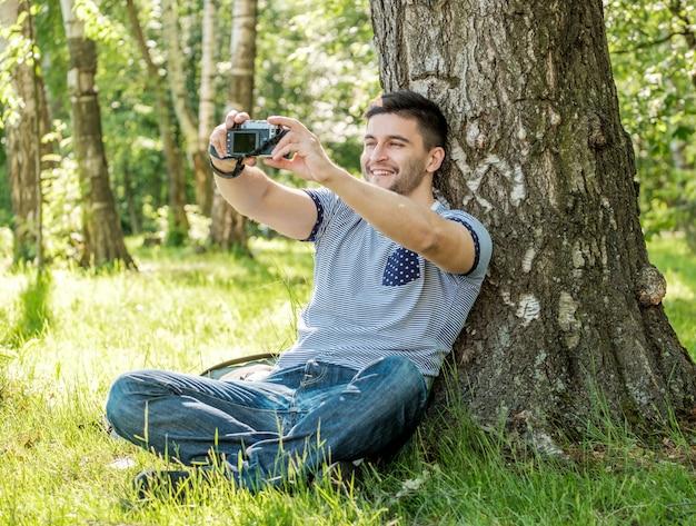 Retrato de hombre joven inconformista con cámara al aire libre. joven fotógrafo masculino haciendo selfie en día de verano.