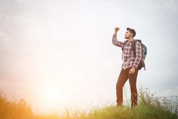 Retrato de hombre joven inconformista que levanta las manos al aire libre con backpac