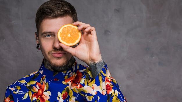 Retrato de un hombre joven inconformista que sostiene la naranja jugosa delante de sus ojos