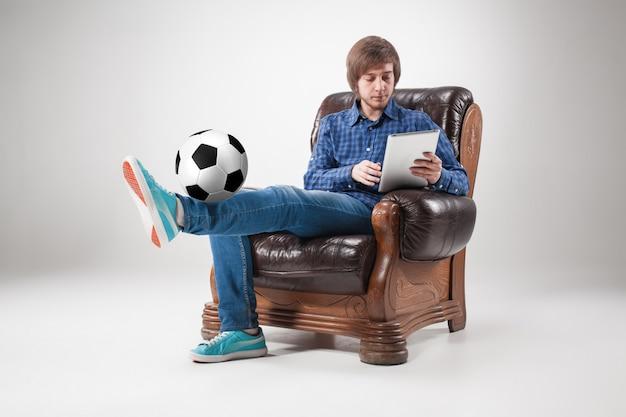 Retrato de hombre joven con laptop y pelota de futbol