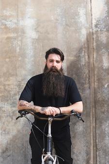 Retrato de un hombre joven con una larga barba sentada frente a un fondo de concreto