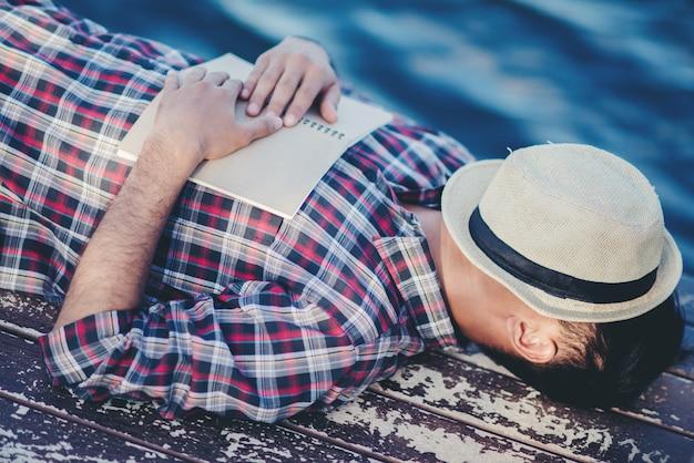 Retrato de hombre joven libro cubierta la somnolencia provoca el sueño.
