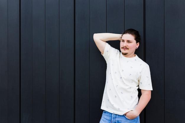 Retrato de un hombre joven con la mano en la cabeza y la mano en el bolsillo de pie contra la pared