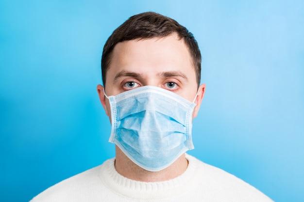 Retrato de hombre joven con máscara médica en azul. concepto de coronavirus. protección respiratoria