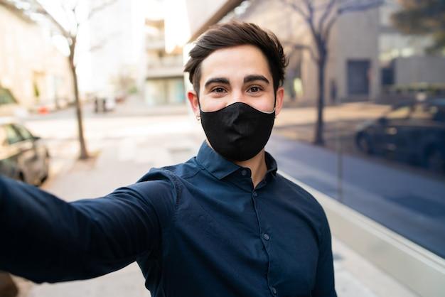 Retrato de hombre joven con máscara protectora y tomando un selfie mientras está de pie al aire libre en la calle. nuevo concepto de estilo de vida normal.