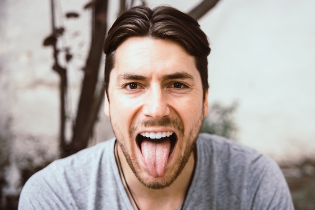 Retrato de hombre joven modelo con cara graciosa sacando la lengua