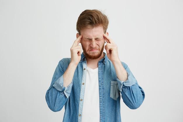 Retrato de hombre joven molesto disgustado frunciendo el ceño sosteniendo los dedos en las sienes sobre fondo wite. ojos cerrados.