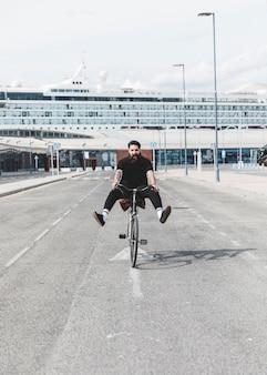 Retrato de hombre joven montando bicicleta en una carretera con las piernas expulsadas delante de un crucero