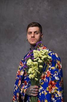Retrato de un hombre joven con orejas y nariz perforadas que sostienen flores amarillas y púrpuras del limonium contra fondo gris