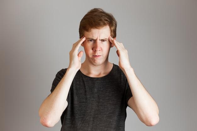 Retrato de hombre joven pelirrojos molesto disgustado frunciendo el ceño sosteniendo los dedos en las sienes. sobre pared gris. copie el espacio.