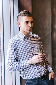 Retrato de un hombre joven pensativo que se inclina en la ventana que sostiene el vidrio de cerveza disponible