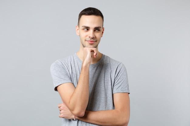 Retrato de hombre joven pensativo en ropa casual mirando a un lado y poner la mano apuntando hacia arriba en la barbilla