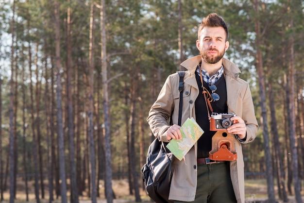 Retrato de un hombre joven de pie en el bosque con mapa y cámara vintage
