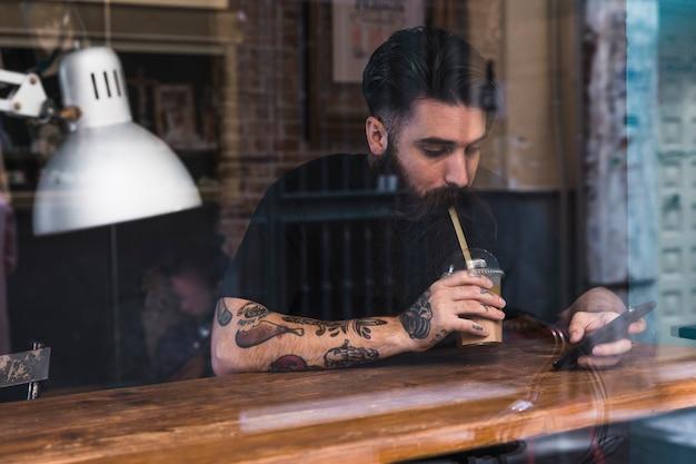 Retrato del hombre joven que bebe la leche del chocolate usando el teléfono móvil en café