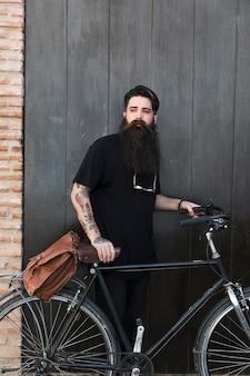Retrato de un hombre joven que se coloca con la bicicleta delante de la puerta negra cerrada