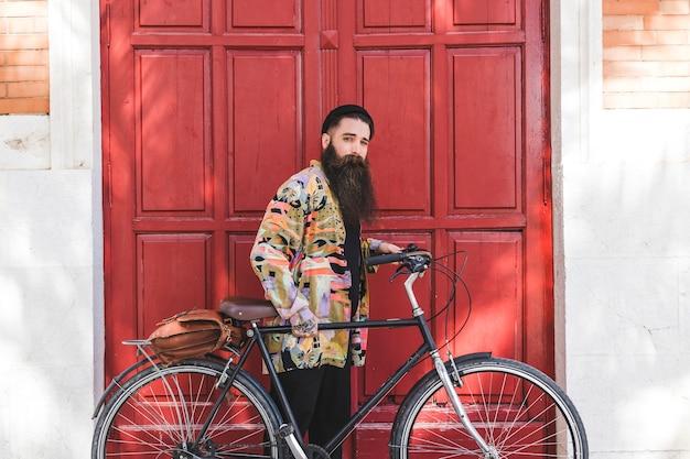 Retrato de un hombre joven que se coloca con la bicicleta delante de la puerta roja