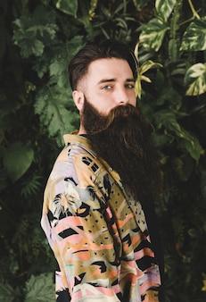 Retrato de un hombre joven que se coloca delante de las plantas que miran la cámara