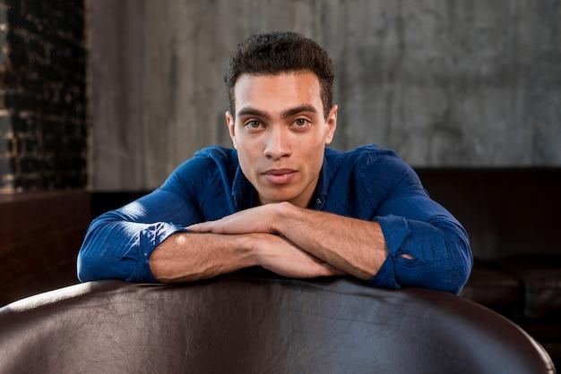 Retrato de un hombre joven que se inclina al borde del sofá que mira la cámara