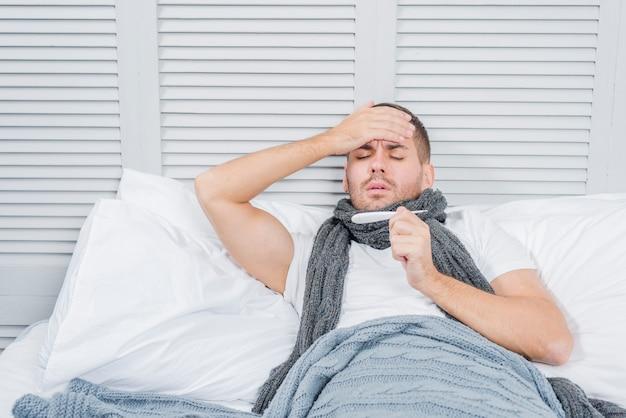 Retrato del hombre joven que miente en cama que comprueba su fiebre en termómetro