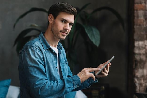 Retrato del hombre joven que mira que sostiene la tableta digital disponible que mira la cámara