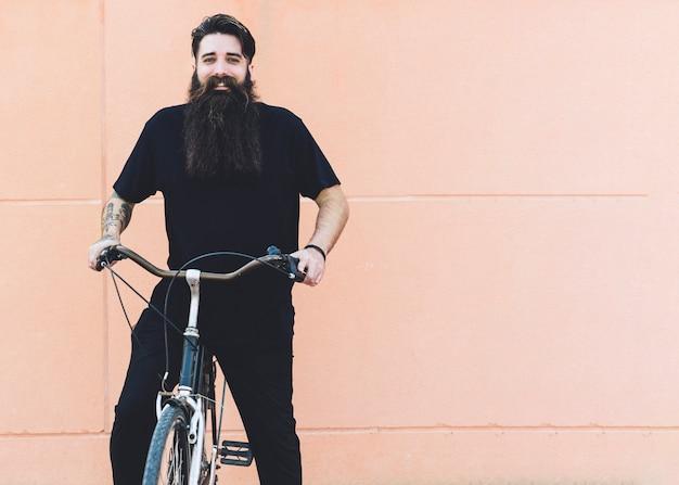 Retrato de un hombre joven que monta en la bicicleta contra fondo beige