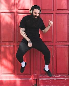 Retrato de un hombre joven que salta en aire con los auriculares en su oído contra la puerta roja