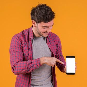 Retrato de un hombre joven que señala su dedo en el teléfono móvil contra un contexto anaranjado