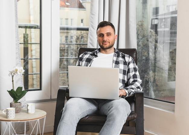 Retrato de un hombre joven que se sienta en la butaca usando el ordenador portátil en casa