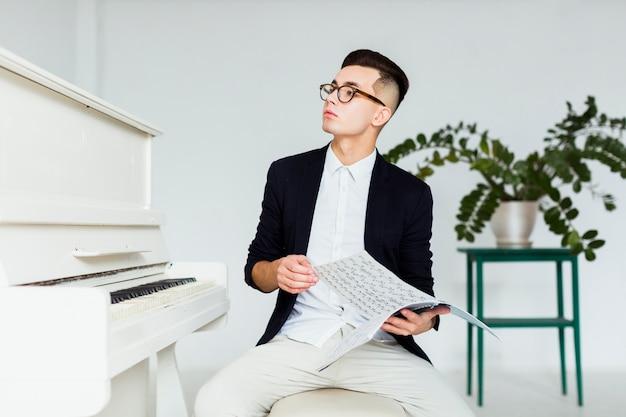 Retrato de un hombre joven que se sienta cerca del piano que sostiene la hoja musical que mira lejos