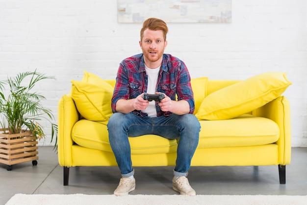Retrato de un hombre joven que se sienta en el sofá amarillo en la sala de estar que juega el videojuego