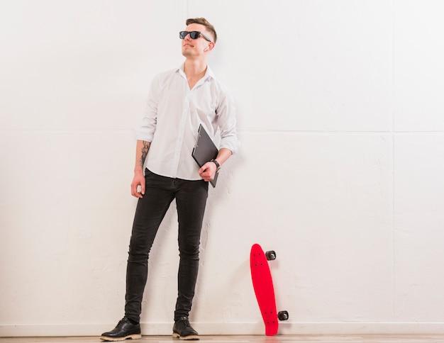 Retrato de un hombre joven que sostiene el sujetapapeles en la mano que se coloca cerca del monopatín que se opone a la pared blanca