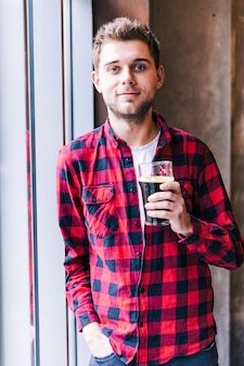 Retrato de un hombre joven que sostiene el vidrio de cerveza que mira la cámara