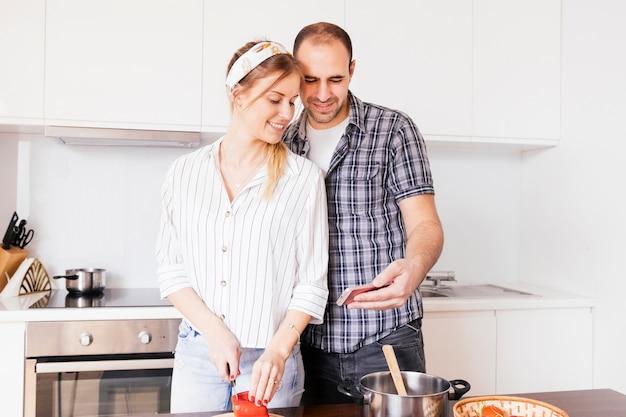 Retrato de un hombre joven que toma selfie en el teléfono móvil con su esposa corte vegetal con cuchillo