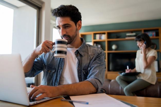 Retrato de hombre joven que trabaja con una computadora portátil desde casa mientras la mujer habla por teléfono
