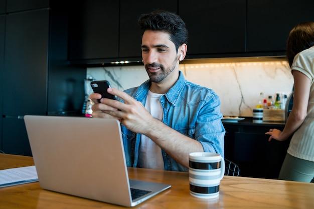 Retrato de hombre joven que trabaja con una computadora portátil y un teléfono móvil desde casa mientras la mujer cocina en segundo plano.