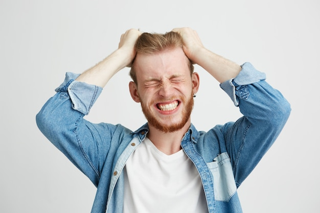 El retrato del hombre joven de la rabia enojada que tocaba su pelo apretó los dientes sobre fondo del wite. ojos cerrados.