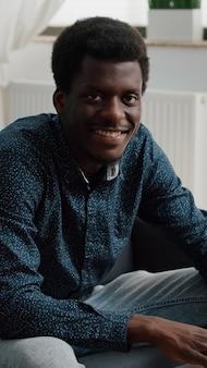 Retrato de hombre joven en la sala de estar escribiendo en el portátil, mirando a la cámara y sonriendo