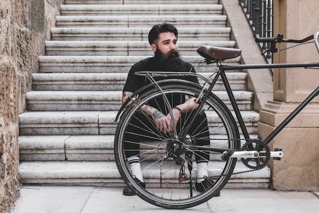 Retrato de un hombre joven sentado en la escalera con bicicleta