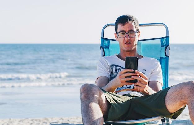 Retrato de hombre joven sentado en la hamaca mirando teléfono inteligente en la playa