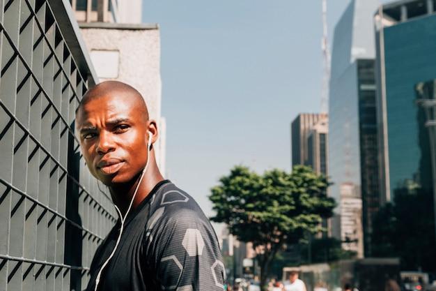 Retrato de un hombre joven serio de la aptitud con el auricular en su oído que se coloca en la ciudad